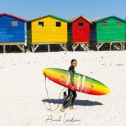 Surfeuse devant les cabanes de plage